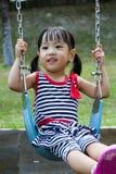 Oscillation asiatique d'enfant au parc Photos stock