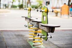 Oscillation colorée dans un terrain de jeu d'enfants Grenouille formée Photos libres de droits