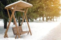 Oscillation de banc en bois en parc d'hiver photos stock