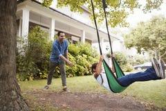 Oscillation de jardin de Pushing Daughter On de père à la maison photos stock