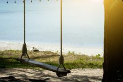 Oscillation en bois sur la plage avec le coucher du soleil photos libres de droits