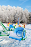 Oscillation et glissière couvertes par neige au terrain de jeu Photo stock