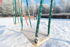 Oscillation et glissière couvertes par neige au terrain de jeu dedans Photographie stock