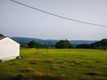 Oscillation rouge au milieu d'un ranch Champ d'herbe verte avec des montagnes photo stock