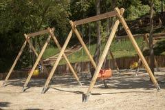 Oscillazione del campo da giuoco Pali di legno e sedili di plastica fotografie stock libere da diritti
