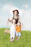 Oscillazione della famiglia contro il cielo e l'erba Fotografie Stock