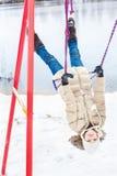 Oscillazione di guida della ragazza sottosopra sullo stagno di inverno Immagine Stock