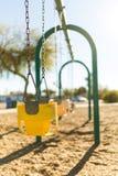 Oscillazione gialla del parco del gioco del ` s del bambino Immagini Stock