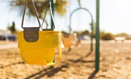 Oscillazione gialla del parco del gioco del ` s del bambino con fondo sfuocato Fotografie Stock