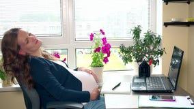 Oscillazione rilassata della donna incinta sul suo posto di lavoro della sedia all'ufficio stock footage