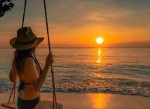 Oscillazione sexy del cappello del bikini e di paglia di usura di donna le oscillazioni alla spiaggia tropicale sulle vacanze est immagine stock libera da diritti