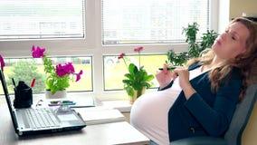 Oscillazione stanca della donna incinta sulla sedia vicino al computer nel posto del lavoro d'ufficio video d archivio