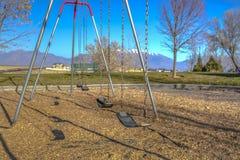 Oscillazioni ad un campo da giuoco che getta le ombre sulla terra un giorno soleggiato fotografia stock