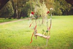 Oscillazioni decorate con i nastri e fiori che appendono su un albero in un parco di estate fotografia stock libera da diritti