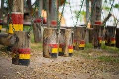 Oscillazioni di legno di Colouful nella fila Campo da giuoco esterno dei bambini fotografie stock