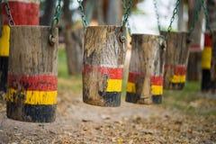 Oscillazioni di legno di Colouful nella fila Campo da giuoco esterno dei bambini fotografie stock libere da diritti