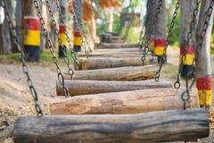 Oscillazioni di legno nella fila Campo da giuoco esterno dei bambini immagini stock