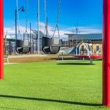Oscillazioni e banchi quadrati del bambino su un campo da giuoco osservato un giorno soleggiato fotografia stock