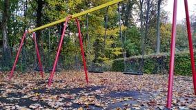 Oscillazioni nel parco dei bambini con le foglie di autunno Immagini Stock