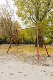Oscillazioni in un parco con le foglie cadute gialle degli alberi fotografie stock libere da diritti