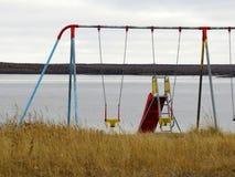 Oscillazioni variopinte dei bambini sulla linea della costa in Kuujjuaq fotografia stock