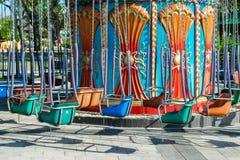 Oscillazioni variopinte del metallo sulle catene in un parco di divertimenti senza gente immagine stock