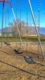 Oscillazioni verticali ad un campo da giuoco che getta le ombre sulla terra un giorno soleggiato fotografia stock