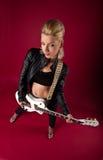 Oscillez la femme dans la guitare de pose en cuir noire de petit morceau Images libres de droits