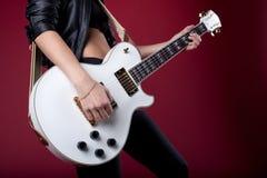 Oscillez le femme en cuir noir posant avec la guitare Photos stock