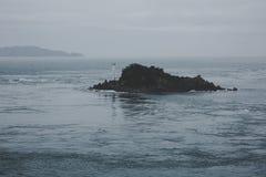 Oscilli con un faro nel mare, i mulinelli Naruto Fotografia Stock
