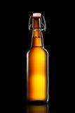 Oscilli la bottiglia superiore della birra leggera isolata su fondo nero Immagini Stock