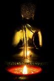 Oscuridad de N de la luz de la vela con la estatua de oro trasera de Buda en el fondo Imagen de archivo