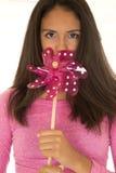 Oscuridad linda - muchacha adolescente complected que sostiene un molino de viento del juguete Foto de archivo libre de regalías