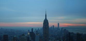 Oscuridad o salida del sol del sykline de New York City rojos de azules y ora amarillo imagen de archivo