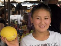 Laughing young market woman, melon in hand stock image
