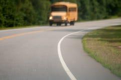 Oskarp abstrakt sikt av skolbussen som kör på vägen Arkivfoton