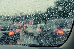Oskarp bil som ses till och med den våta vindrutan Arkivfoto