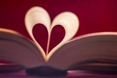 Oskarp hjärta som göras från boksidor över röd bakgrund Arkivfoton