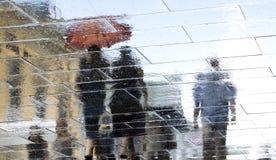 Oskarp regnig reflexionskontur av folk som går, och sunn arkivfoton
