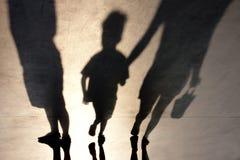 Oskarp skugga av person två och en unge arkivfoto