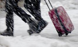 Oskarpa ben av att gå för två personer som är snabbt i resväska för tungt snöfall och för rullning röd royaltyfri bild