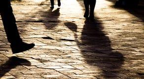 Oskarpa benkonturer och skuggor av folk som går i solnedgång royaltyfri fotografi