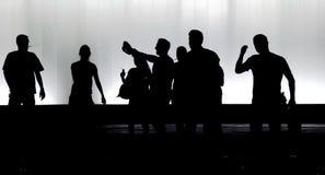 Oskarpa konturer av ungdomarsom går i den svartvita natten arkivbilder