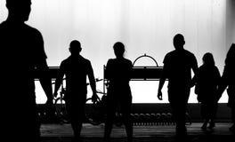 Oskarpa konturer av ungdomarsom går i den svartvita natten arkivfoton
