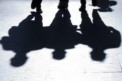 Oskarpa konturer och skuggor av tre personer som går stadsstre fotografering för bildbyråer
