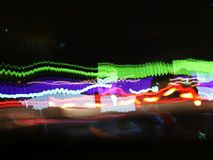 Oskarpa ljus av bilar på stadsgator på natten, ljus skuggar från transport - rusningstid arkivbild