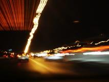 Oskarpa ljus av bilar på stadsgator på natten, ljus skuggar från transport - rusningstid arkivfoton