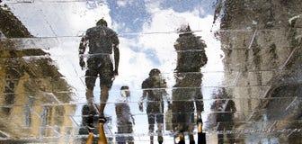 Oskarpa reflexionskonturer av folk som går på en regnig dag royaltyfria bilder