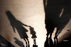 Oskarpa skuggor av modern med gå för barn arkivfoto