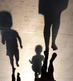 Oskarpa skuggor av modern med två litet barnungar arkivbild